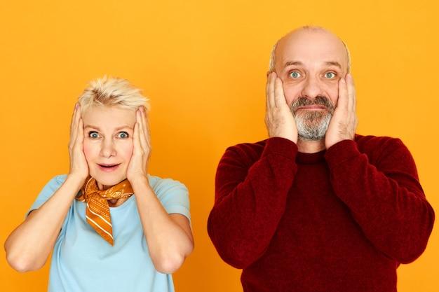 Shock, verbazing en verrassing concept. grappige europese bebaarde senior mannelijke en blonde vrouw wordt geschokt door verbazingwekkend onverwacht nieuws, hand in hand op de wangen, mond wijd openhoudend
