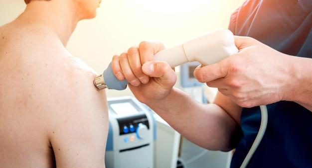 Shock wave therapie. het magnetische veld, revalidatie. fysiotherapeut arts voert een operatie uit aan de schouder van een patiënt