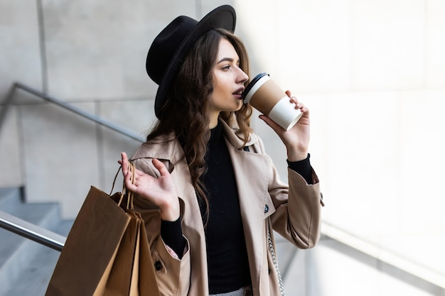 Shop dag. koffiepauze. aantrekkelijke jonge vrouw die met papieren zakken op straat loopt.