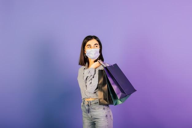 Shopaholic in beschermend chirurgisch masker op gezicht met papieren zakken in de hand geïsoleerd op violette achtergrond.