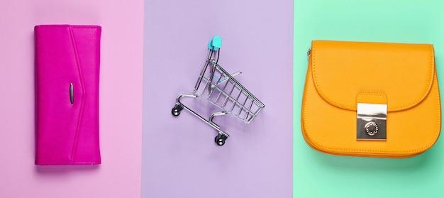 Shopaholic minimalistisch concept. tas, portemonnee, mini winkelwagentje op pastel achtergrond. bovenaanzicht