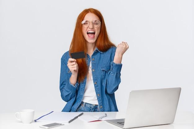 Shopaholic opgewonden omdat hij geweldige korting kreeg, cashback na online aankoop, vuistpomp die tevreden ja schreeuwt, creditcard vasthoudt en laptop gebruikt om op internet te kopen, witte achtergrond