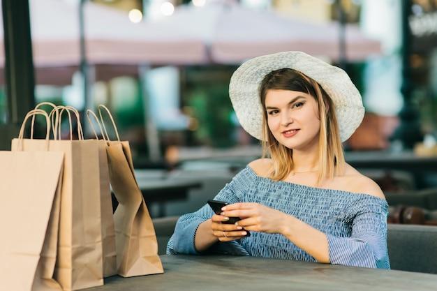Shopaholic vrouw in stijlvolle jurk en hoed zit aan tafel op terras en maakt gebruik van een smartphone