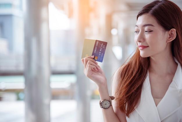 Shopaholic vrouw met boodschappentassen, geld, creditcard bij winkelcentra