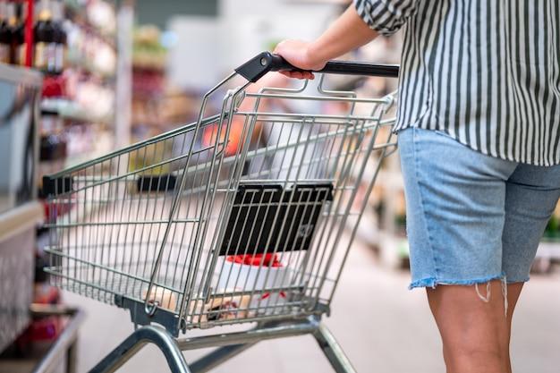 Shopper met winkelwagentje in de supermarkt. eten kopen in de supermarkt. boodschappen doen