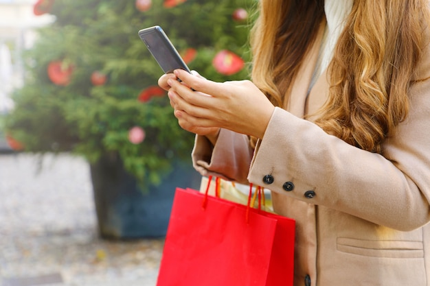 Shopper vrouw draagtassen met behulp van slimme telefoon om online te winkelen in de kersttijd.