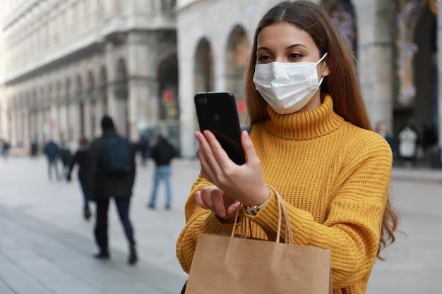 Shopper vrouw met chirurgisch masker met behulp van slimme telefoon-app in stadsstraat