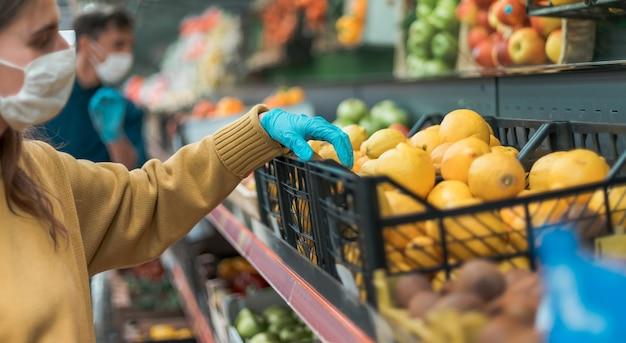 Shoppers in beschermende maskers die fruit kiezen in de supermarkt. coronavirus in de stad