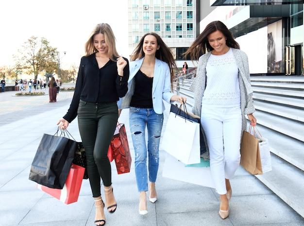 Shopping concept - mooie meisjes met boodschappentassen wandelen in het winkelcentrum