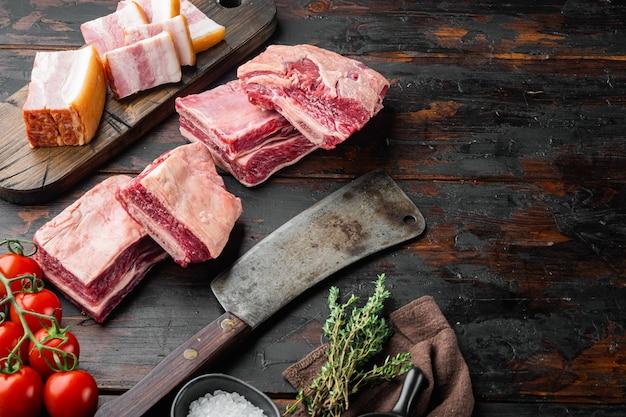 Short ribs bone in stoofpot, met ingrediënten, en oud slagersmes, op oude donkere houten tafel