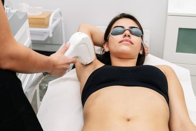 Short shot schoonheidsspecialiste die een laserdiodebehandeling geeft aan een vrouw in de oksel waar de cliënt een laserbeschermingsbril draagt