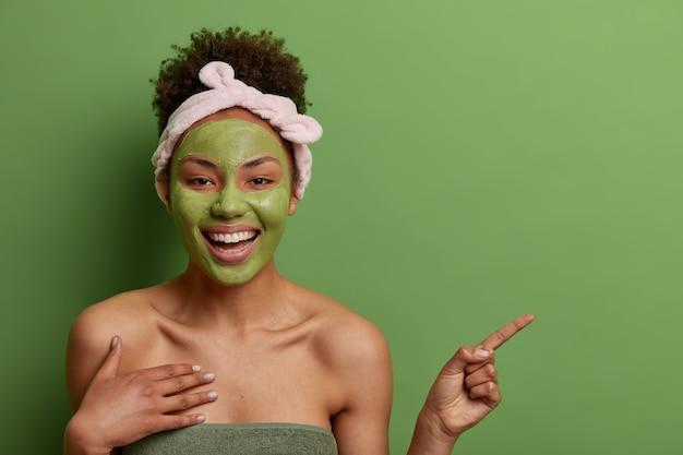 Shot van aangenaam uitziende vrolijke afro-amerikaanse vrouw schoonheidsmasker toepast op het gezicht, cosmetologieproduct aanbeveelt, geeft op kopie ruimte aan, geïsoleerd op groene muur. huid zorg concept