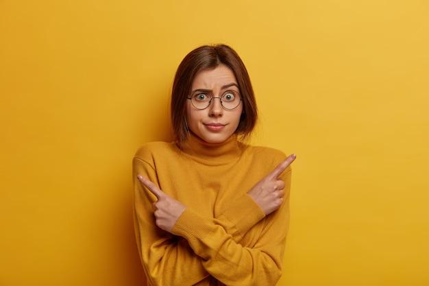 Shot van beschaamde, onbewuste vrouw wijst zijwaarts, denkt wat te kiezen, trekt wenkbrauwen op, wijst naar rechts en links, gekleed in een gele outfit, staat besluiteloos binnen. moeilijke keuze