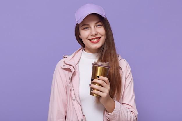 Shot van blije vrouwelijke student heeft koffiepauze na lezingen, geniet van warme drank uit thermos mok