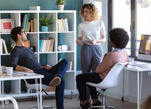 Shot van casual jonge zakenmensen die met de digitale tablet werken terwijl ze in het nieuwe kantoor praten.