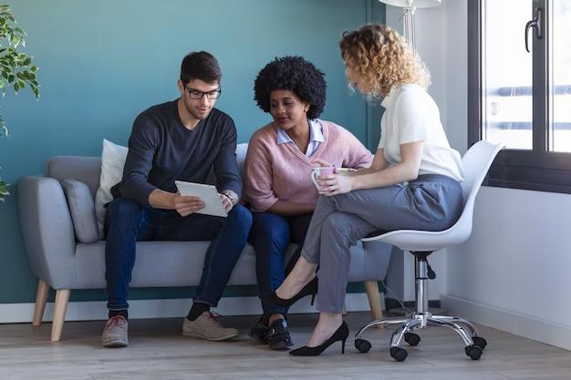 Shot van casual jonge zakenmensen die met de digitale tablet werken terwijl ze in het nieuwe kantoor zitten.