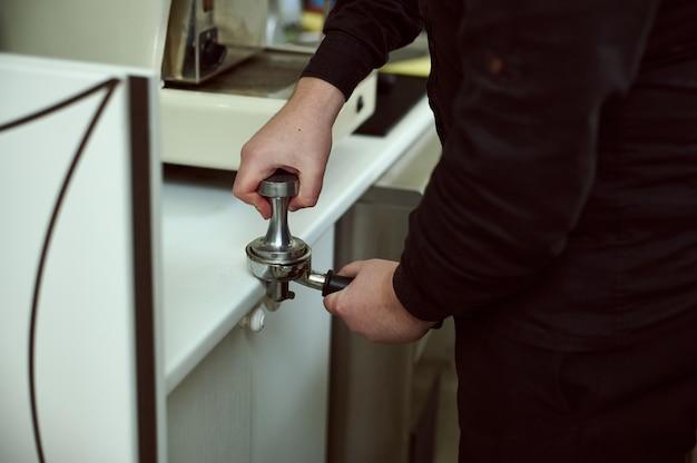 Shot van de hand van barista koffie tamper te houden en koffie te bereiden