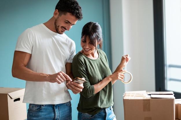 Shot van een aantrekkelijk jong stel dat dozen inpakt om naar een nieuwe flat te verhuizen terwijl ze thuis in de woonkamer naar een mobiele telefoon kijkt.