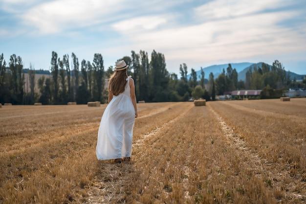 Shot van een aantrekkelijke jonge boerin in een witte jurk in een droog veld van stro