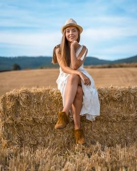 Shot van een aantrekkelijke vrouw in een witte jurk zittend op een hooiberg en kijkend naar de camera