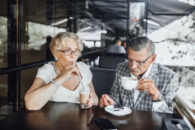 Shot van een bejaarde echtpaar lachen en een kopje koffie samen, zomerterras in modern restaurant.