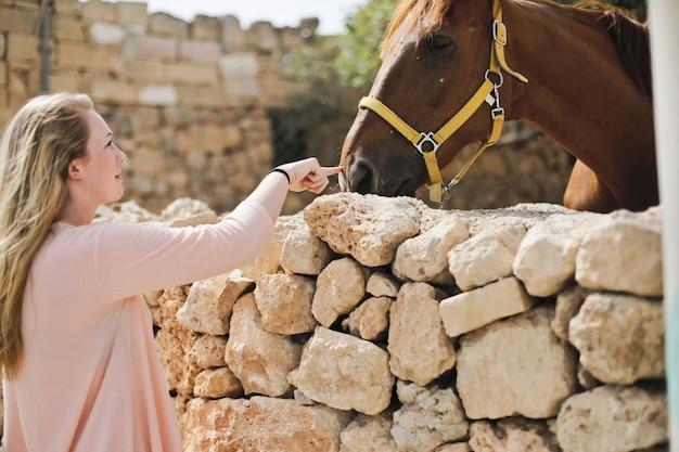 Shot van een blonde vrouw en een bruin paard