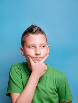 Shot van een emotionele schattige jongen die zijn hoofd bedekt met de hand die moe is hoofdpijn die ware emoties toont