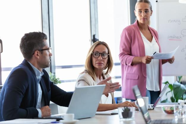 Shot van een geconcentreerd business team dat naar hun partners luistert en met een laptop werkt aan een coworking-ruimte.
