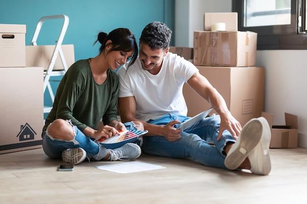 Shot van een gelukkig paar dat kleuren in een kleurenpalet kiest om het appartement te schilderen terwijl ze ideeën zoekt in een digitale tablet die op de vloer zit.