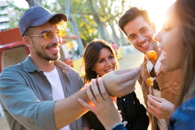 Shot van een gelukkige en aantrekkelijke jonge groep vrienden die fastfood bezoeken en eten op de eetmarkt op straat.