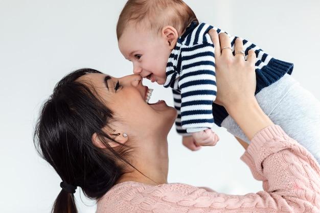 Shot van een gelukkige jonge moeder die haar schattige zoon hoog in de lucht optilt terwijl ze thuis tijd doorbrengt en geniet.