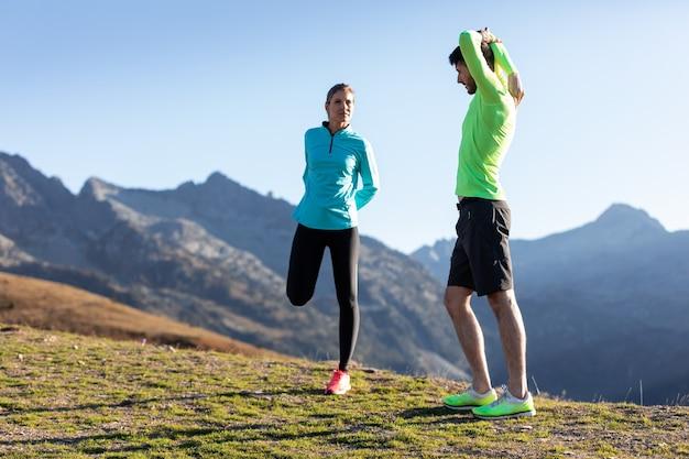 Shot van een gezond jong stel dat 's ochtends samen rekoefeningen doet op het bergpad.