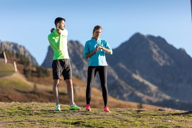 Shot van een gezonde jonge man die rekoefeningen doet terwijl zijn vriendin haar smartwatch op de berg gebruikt.