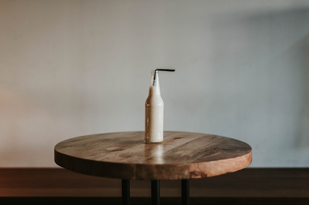 Shot van een glazen fles met een zwart rietje gevuld met een drankje op een bruin houten tafel