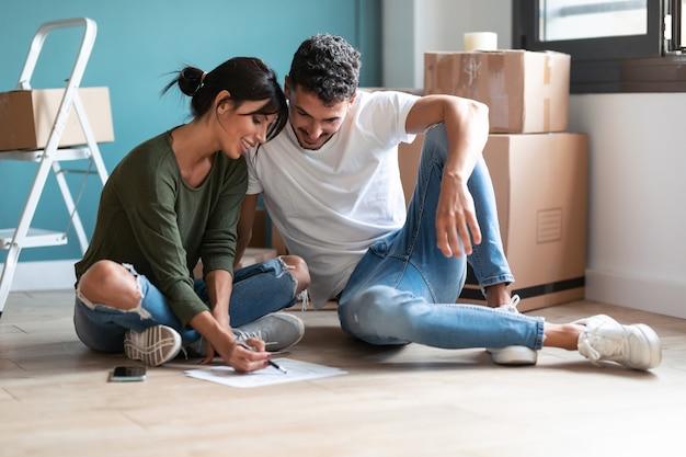 Shot van een jong aantrekkelijk stel dat tekent naar de blauwdrukken van hun nieuwe huis terwijl ze praten over de toekomst zittend op de vloer.