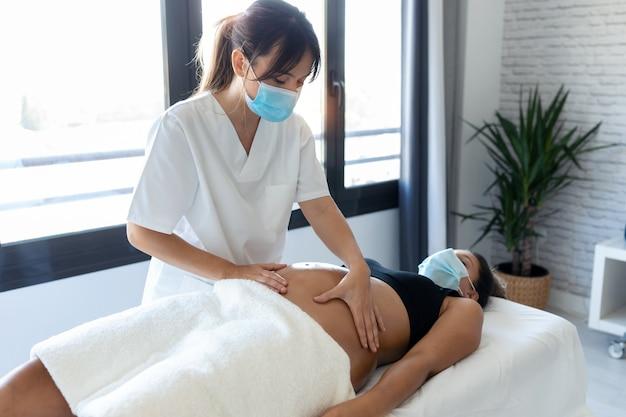 Shot van een jonge fysiotherapeut vrouw die buik masseert op zwangere vrouw op een brancard thuis. vrouwen die een chirurgisch masker en een nieuw normaal concept dragen.