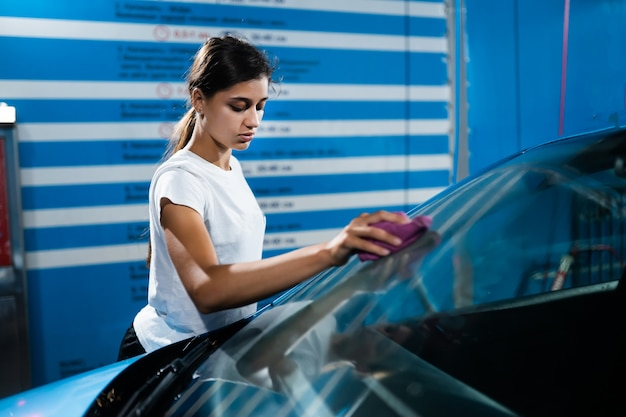 Shot van een jonge vrouw die haar auto schoonmaakt