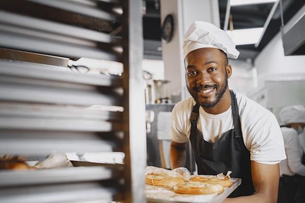 Shot van een knappe bakker die dienbladen met vers brood op de stand zet bij het bakken. afro-amerikaans.