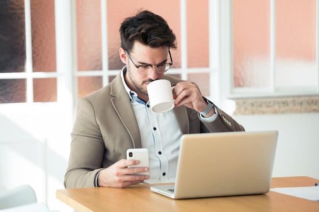 Shot van een knappe jonge zakenman die zijn smartphone gebruikt terwijl hij koffie drinkt voor een laptop op kantoor.