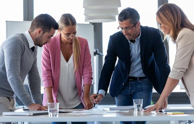 Shot van een knappe zakenman die praat met collega's in de vergadering over coworking space.