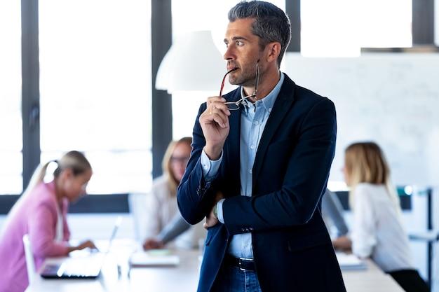 Shot van een knappe zakenman die zijwaarts kijkt terwijl zijn collega's aan een coworking-plek werken.