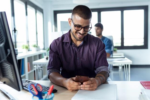 Shot van een lachende jonge zakenman die zijn smartphone gebruikt tijdens het werken met de computer in het moderne opstartkantoor.