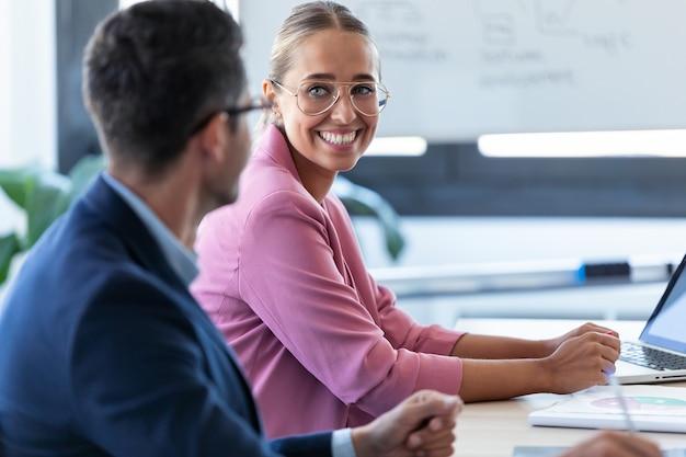 Shot van een lachende jonge zakenvrouw die naar haar partner kijkt en luistert op coworking-ruimte.