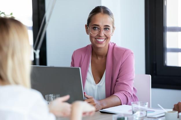 Shot van een lachende jonge zakenvrouw die naar haar partner luistert terwijl ze met een laptop op coworking-ruimte werkt.