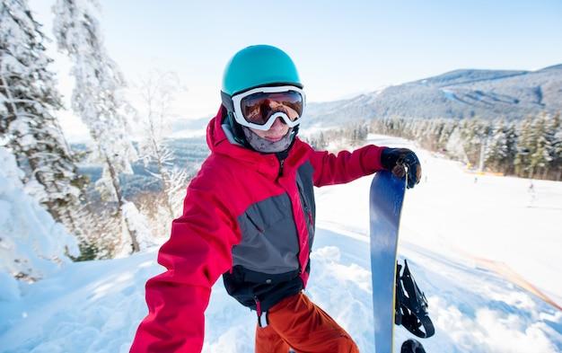 Shot van een man snowboarder die een selfie neemt, staande op de helling van de heuvel in het skigebied op een mooie zonnige winterdag in het skigebied bukovel in de bergen