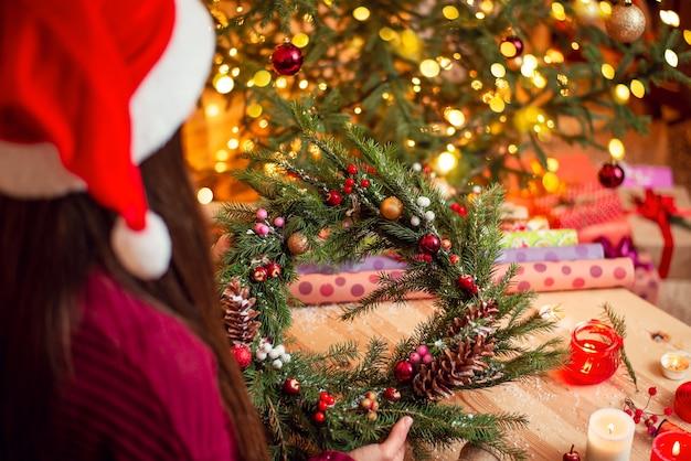 Shot van een meisje met handgemaakte kerstkrans met versierde kerstboom op de achtergrond