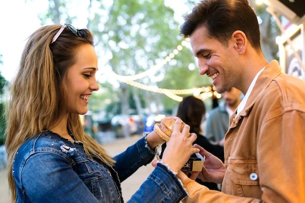 Shot van een mooi aantrekkelijk stel dat samen hamburgers deelt en eet in de eetmarkt op straat.