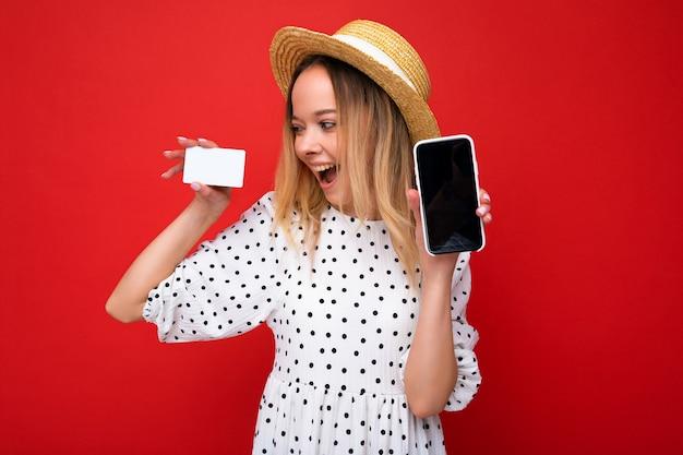 Shot van een mooie, gelukkig lachende blonde vrouw in zomerkleren met een smartphone met een leeg scherm