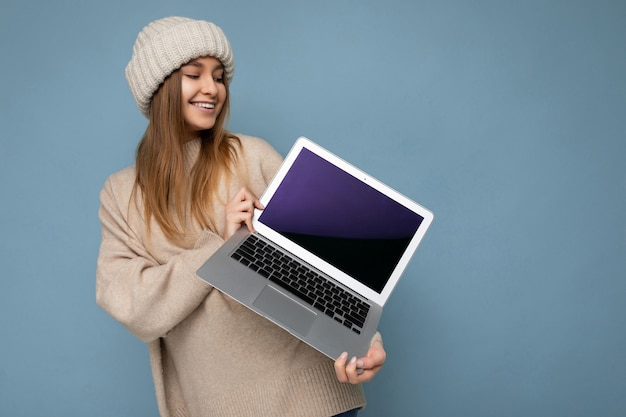 Shot van een mooie glimlachende jonge donkerblonde vrouw in de winter warme gebreide beige hoed met computer