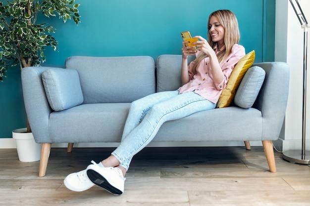 Shot van een mooie jonge vrouw die online winkelt met creditcard en smartphone terwijl ze thuis op de bank zit.